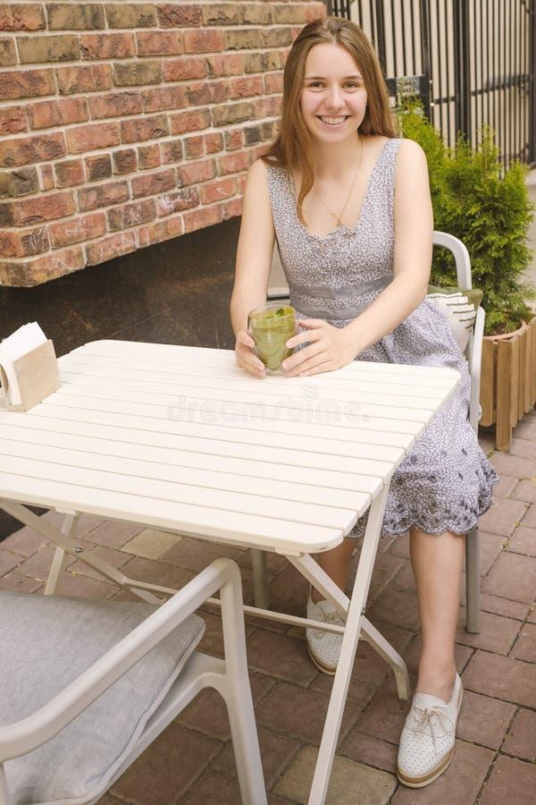 Schönheit sitzender und trinkender Smoothie in einem Café im Freien Mahlzeit des strengen Vegetariers und Detoxkonzept lizenzfreie stockfotografie