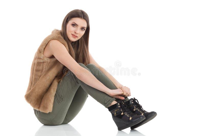 Schönheit sitzt auf einem Boden und betrachtet Kamera lizenzfreie stockfotografie