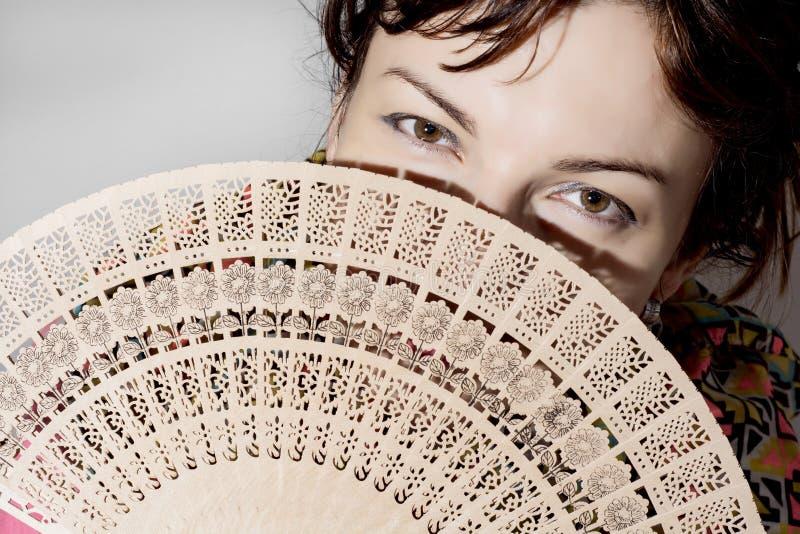 Schönheit teils versteckt hinter einem Fan stockbilder