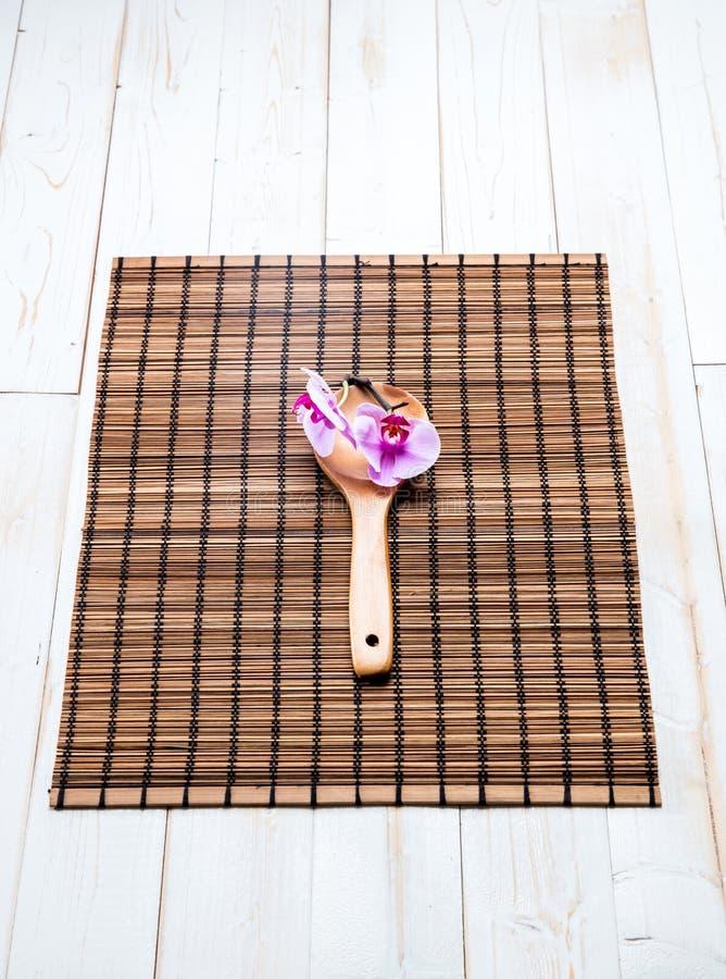 Schönheit und Badekurortkonzept mit hölzernem Löffel und rosa Orchidee stockbilder