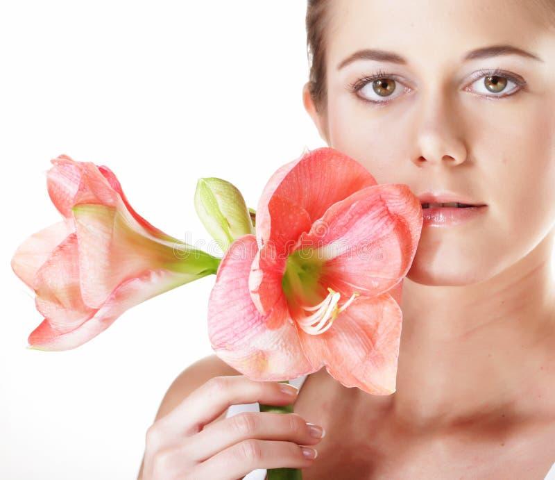 Schönheit und Modekonzept: junge Schönheit mit großen rosa Blumen lizenzfreie stockbilder