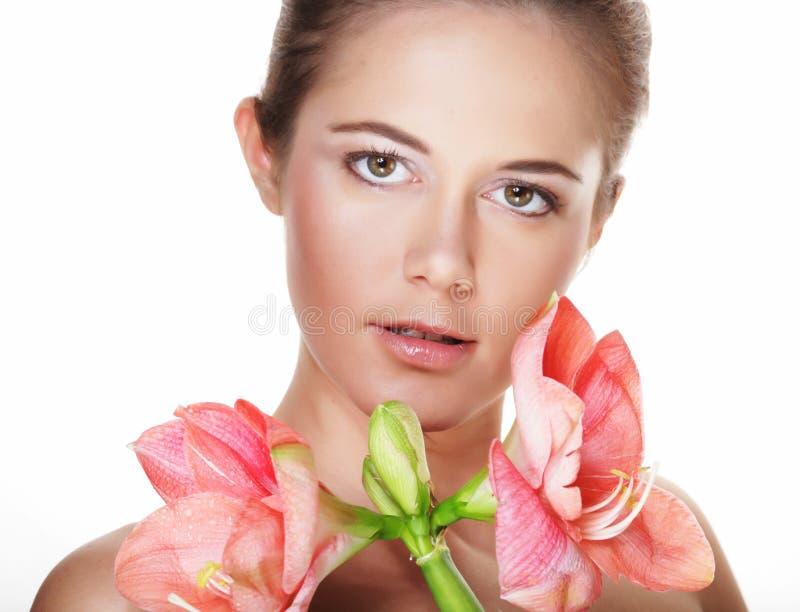 Schönheit und Modekonzept: junge Schönheit mit großen rosa Blumen stockfotografie