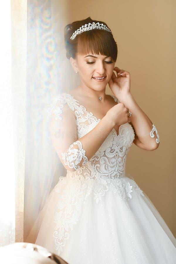 Schönheit und Schmuckkonzept - Frau, die glänzende Diamantohrringe trägt stockfoto
