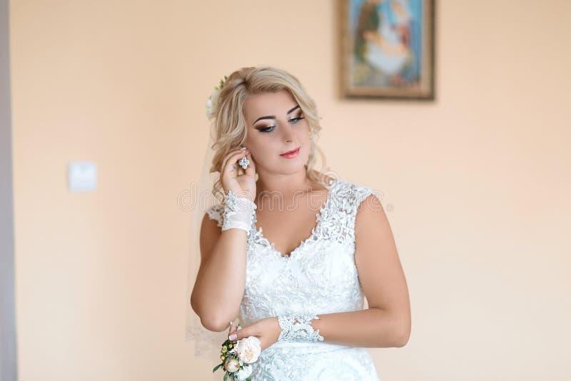 Schönheit und Schmuckkonzept - trägt glänzende Diamantohrringe Frauentragens, die Braut Ohrringe, in einem weißen Heiratskleid un stockfotografie