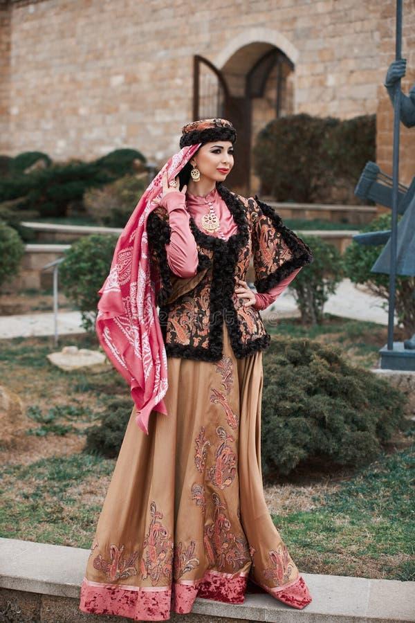 Schönheit, welche die orientalische nationale Kleidungsaufstellung im Freien trägt lizenzfreies stockfoto