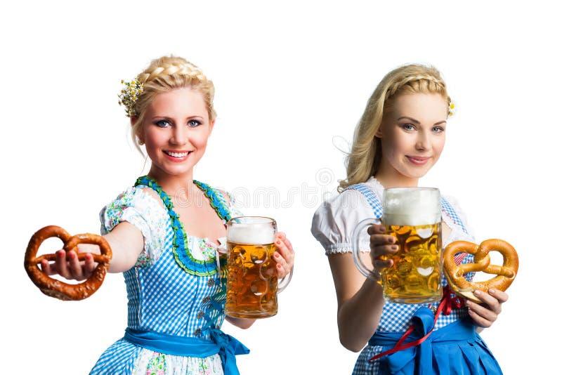 Schönheiten in einem traditionellen bayerischen Dirndl mit Bier und Brezel lizenzfreies stockfoto