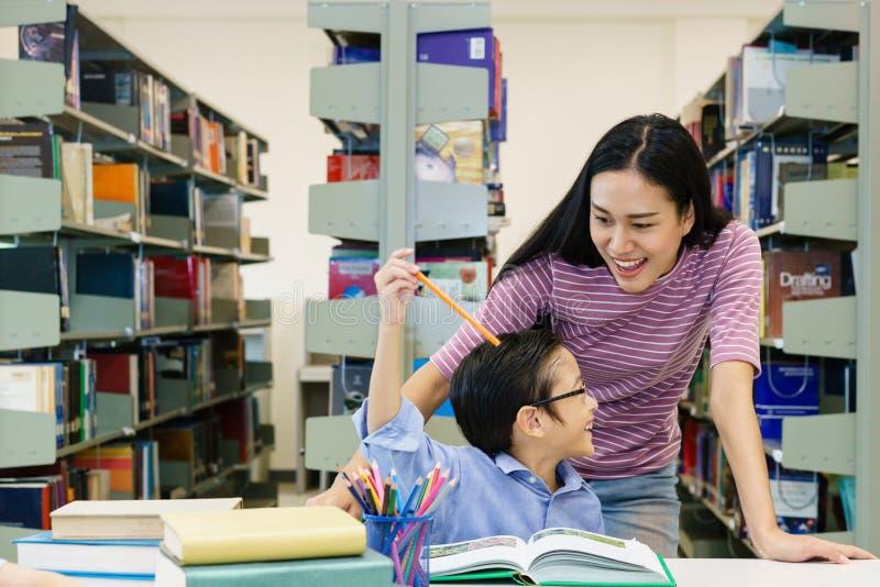 Schönheiten mit Buch des kleinen Jungen Lesezusammen in der Bibliothek stockbild
