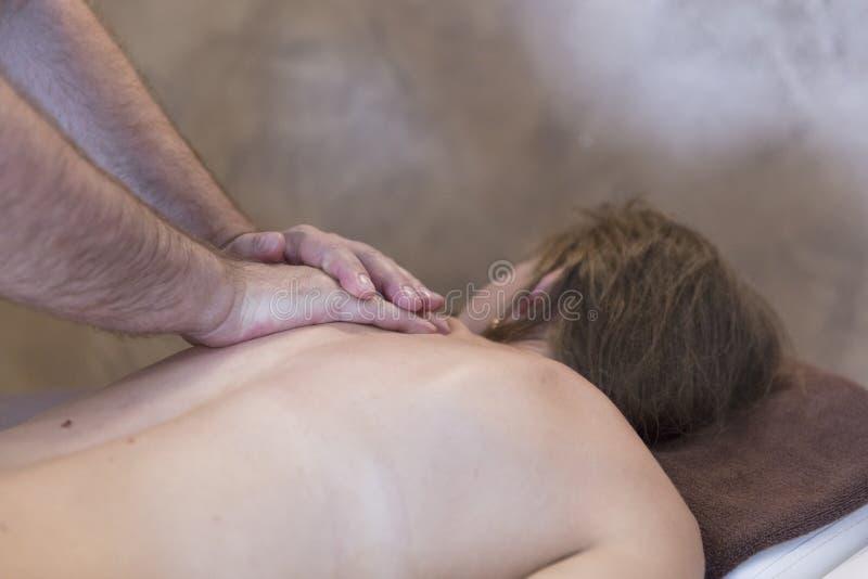 Schönheits-Frau, die Gesichtsmassage erhält Frau, die entspannende Rückenmassage in der Cosmetology-Badekurort-Mitte genießt Körp stockfoto