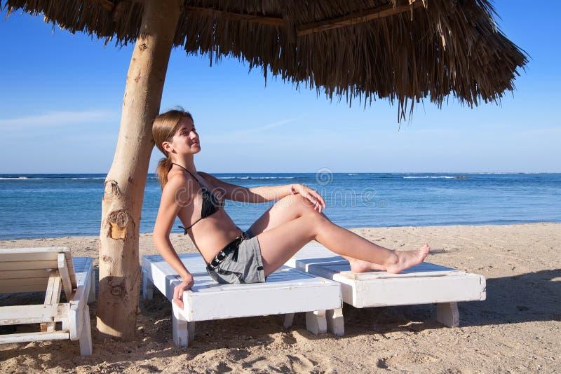 Schönheits-Frau im Bikini, der auf dem Strand sitzt stockbild