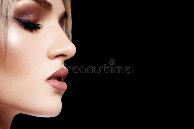Schönheits-Gesicht auf schwarzem Hintergrund mit Kopien-Raum Mode-Make-up, glänzende Haut Glättung des Zauber-Art-Makes-up lizenzfreies stockfoto