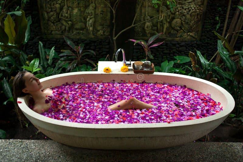 Schönheits-junge Frau, die Bad im im Freien mit tropischer Blume sich entspannt lizenzfreies stockbild