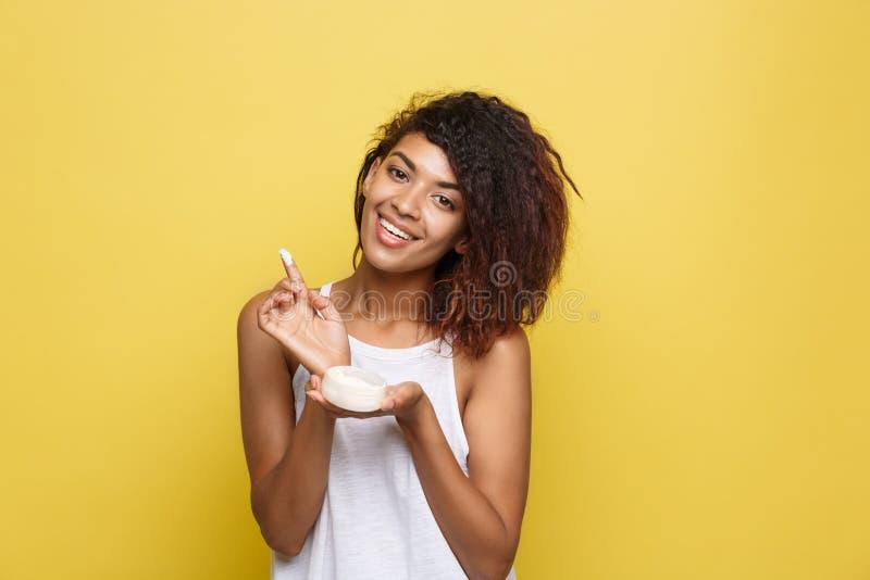 Schönheits-Konzept - schöne junge Afroamerikanerfrau glücklich unter Verwendung der Hautpflegecreme Gelber Studiohintergrund exem stockfoto