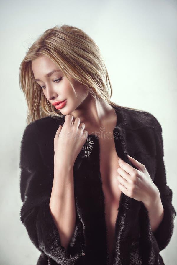 Schönheits-Mode blondes vorbildliches Girl im dunklen Pelz-Mantel stockfoto