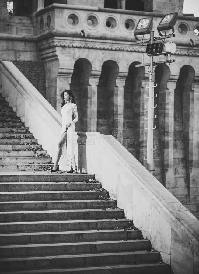 Schönheits-Mode-Modell Girl Art und Weiseblick Junge Frau im weißen langen Kleid Treppenhaus steigernd stockbild