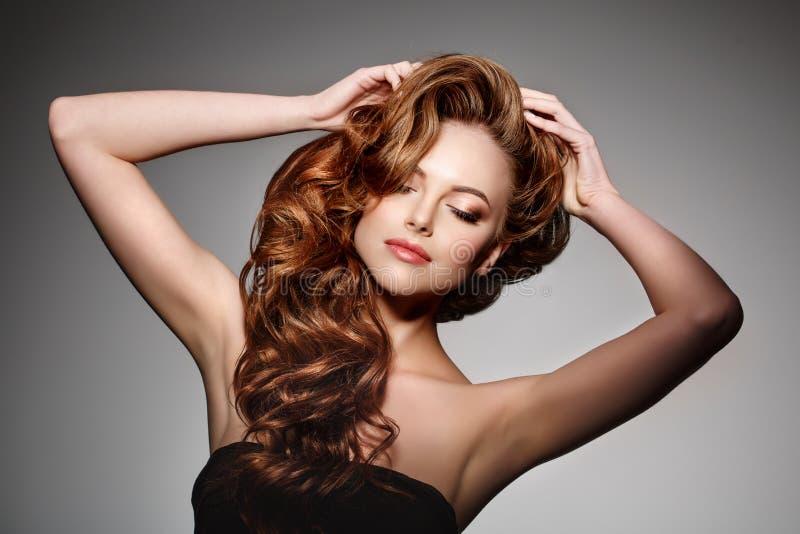 Schönheits-Mode-Modell mit dem langen glänzenden Haar Wellen- u. Lockenvolumen stockfotografie