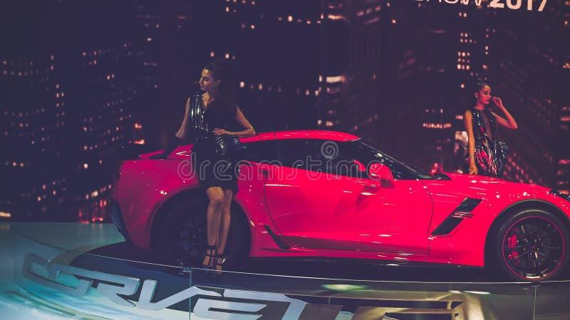 Schönheits-Modell und Rot-Chevrolet Corvette Auto auf Anzeige an Vietnam-Autoausstellung 2017 stockbild