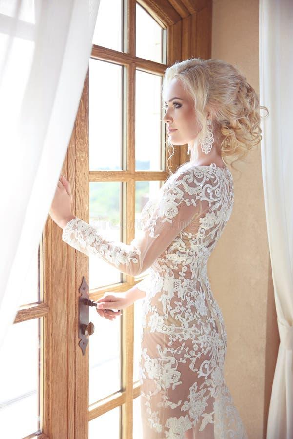Schönheits-Porträt der eleganten Braut im Hochzeitskleid, das Fenster betrachtet lizenzfreie stockbilder