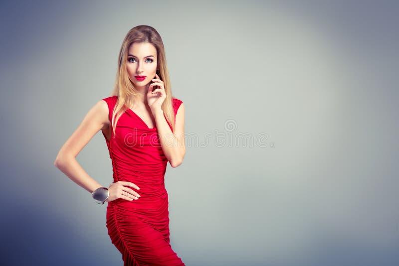 Schönheits-Porträt der Frau im Rot auf Gray Backgound lizenzfreie stockfotografie
