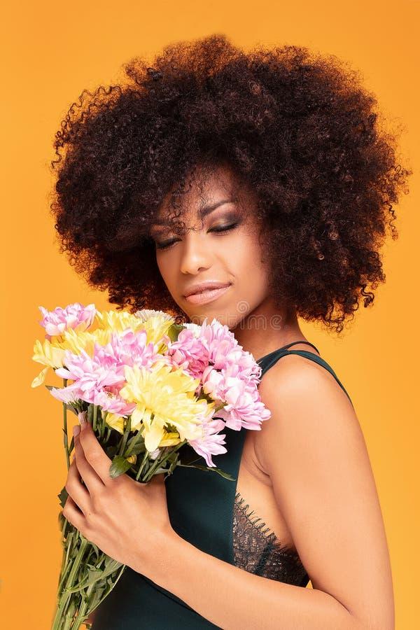 Schönheitsafrofrau mit frischen Blumen stockfotografie