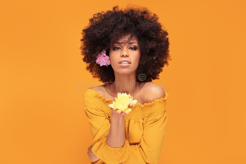 Schönheitsafrofrau mit frischen Blumen stockfoto