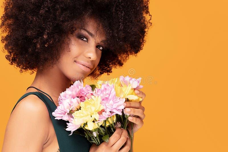 Schönheitsafrofrau mit frischen Blumen stockfotos