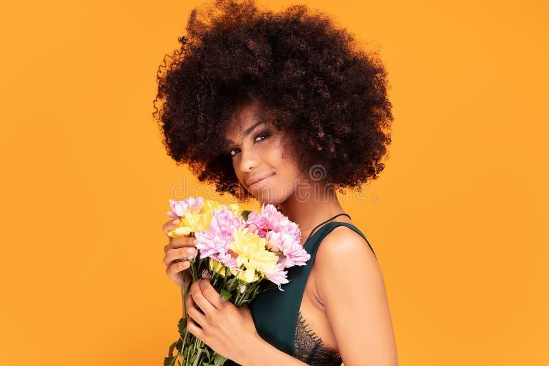 Schönheitsafrofrau mit frischen Blumen lizenzfreies stockfoto