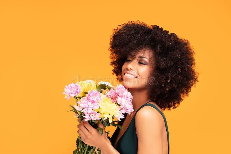 Schönheitsafrofrau mit frischen Blumen lizenzfreie stockfotografie