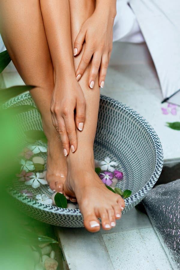 Schönheitsbadekur und -produkt für Frauenfüße und Fußbadekurort Fußbad in der Schüssel mit tropischen Blumen, Thailand stockfotografie