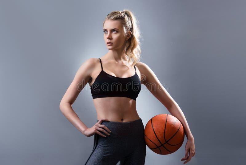 Schönheitsbasketball-spieler, der Basketballball steht und hält stockfotografie