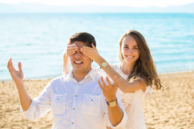 Schönheitsbedeckungsaugen des Freundes lächelnd während beide, die draußen stehen lizenzfreies stockbild