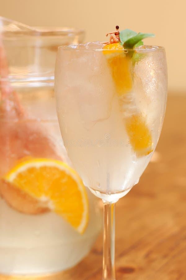 Schönheitsbikini, der auf Zitrusfruchtlimonadenglas sich sonnt Die Auffrischung trinkt Sommerzeitkonzept mit Miniaturmädchenzahl lizenzfreie stockfotografie