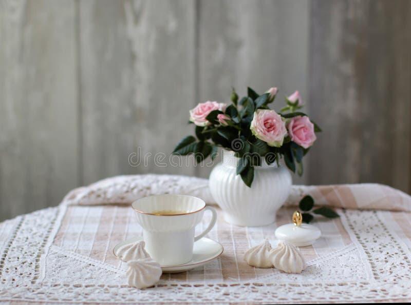 Schönheitsblumenstrauß von Rosen in der weißen Porzellanzuckerschüssel, Porzellanteeschale, Weinleseart, Blumenszene lizenzfreie stockfotografie