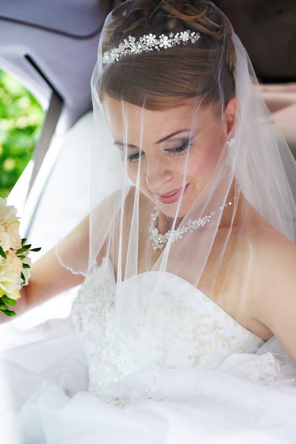Schönheitsbraut in der Hochzeitslimousine lizenzfreie stockbilder