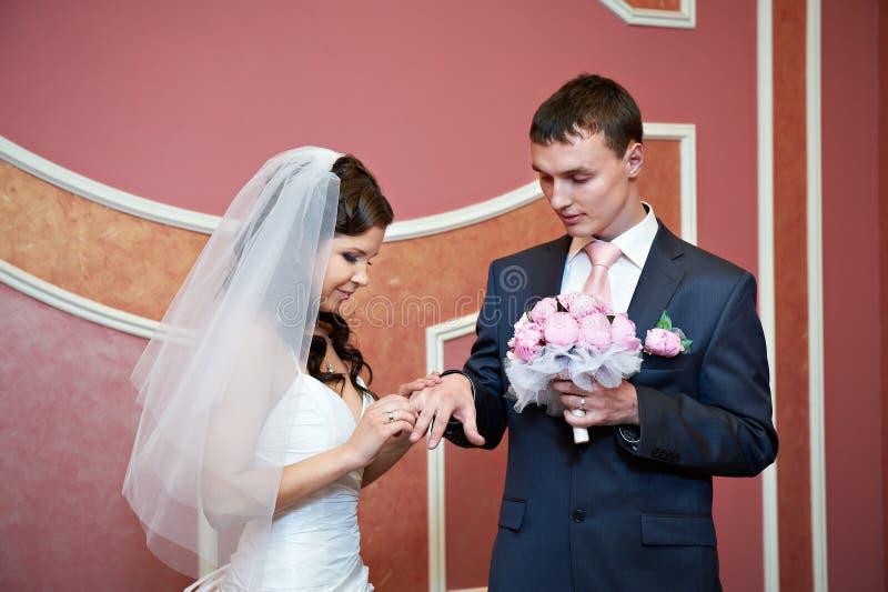 Schönheitsbraut trägt Ehering auf Finger des eleganten Bräutigams lizenzfreies stockfoto