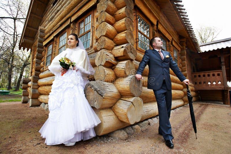 Schönheitsbraut und eleganter Bräutigam nahe altem hölzernem Haus stockbilder