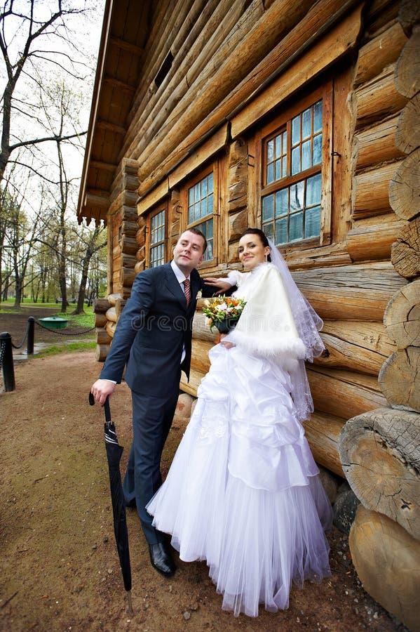 Schönheitsbraut und eleganter Bräutigam nahe altem hölzernem Haus lizenzfreie stockfotografie
