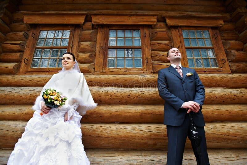 Schönheitsbraut und eleganter Bräutigam nahe altem hölzernem Haus lizenzfreie stockfotos