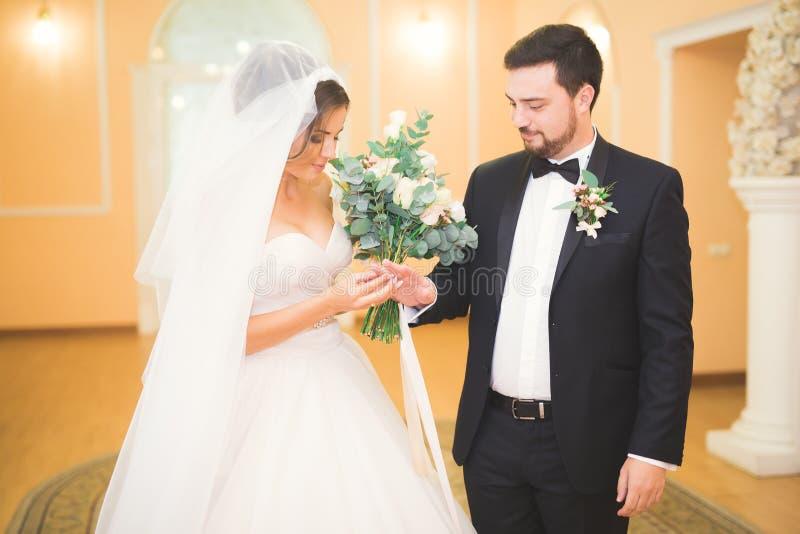 Schönheitsbraut und hübscher Bräutigam tragen sich schellt Hochzeitspaare auf der Trauung lizenzfreie stockfotografie