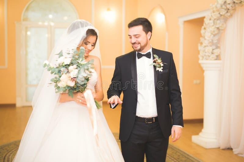 Schönheitsbraut und hübscher Bräutigam tragen sich schellt Hochzeitspaare auf der Trauung stockfotos
