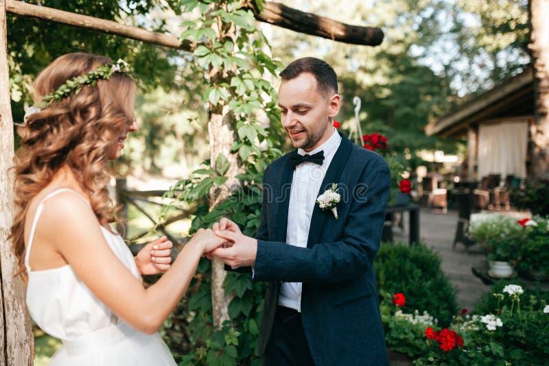 Schönheitsbraut und hübscher Bräutigam tragen sich schellt Hochzeitspaare auf der Trauung stockfoto
