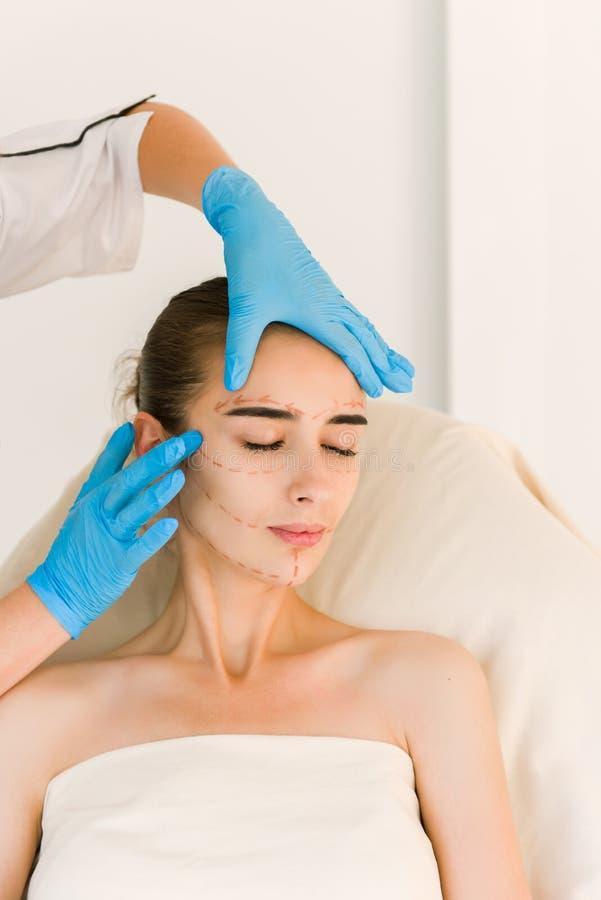 Schönheitschirurg Examining Female Client im Büro lizenzfreie stockbilder