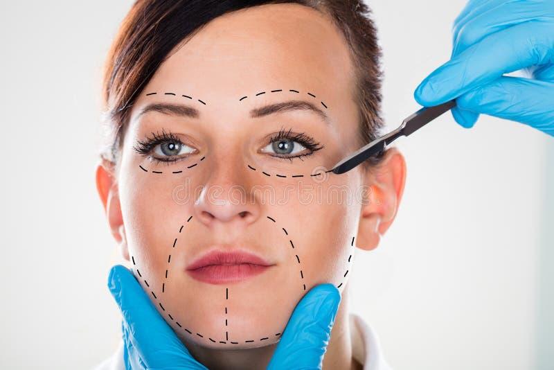 Schönheitschirurgie mit Skalpell auf junger Frau stockfotos