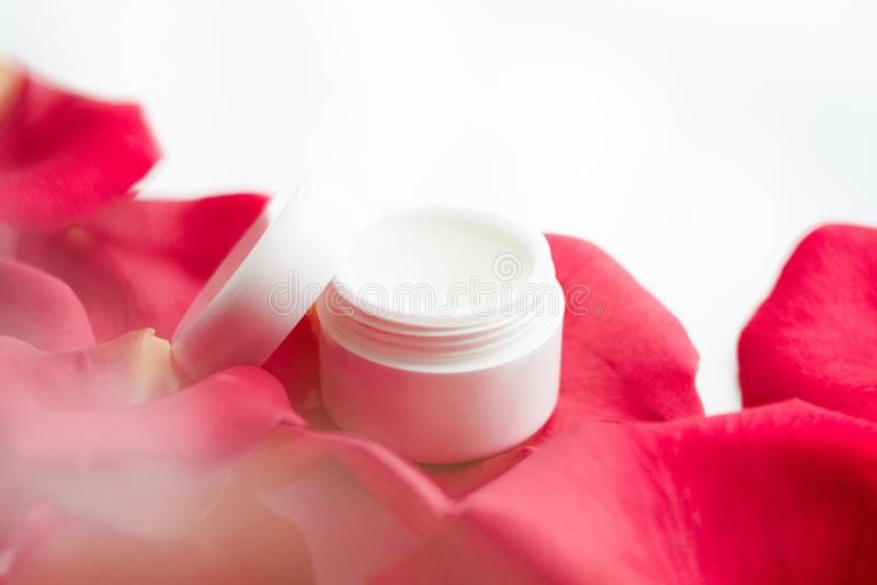 Schönheitscremetiegel und stieg Blumenblätter - Kosmetik mit Blumen redeten Konzept an lizenzfreie stockfotografie