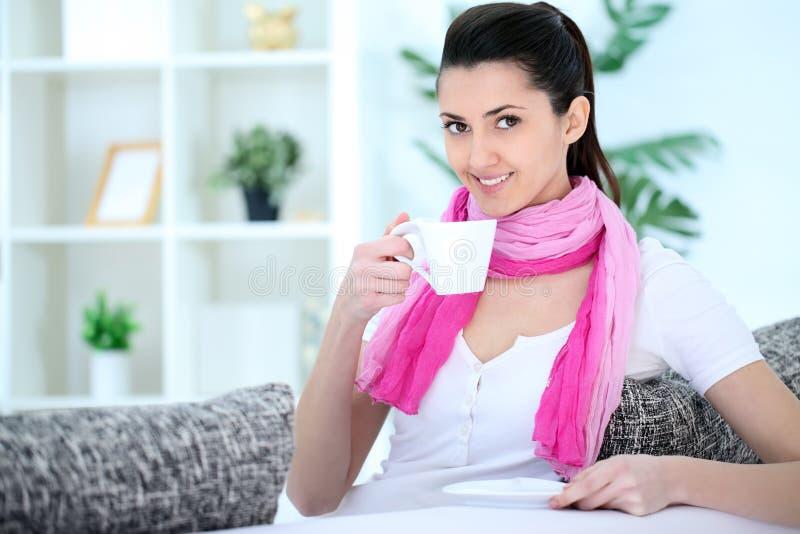 Schönheitsdame, die auf Sofa und trinkendem Kaffee sitzt stockfoto