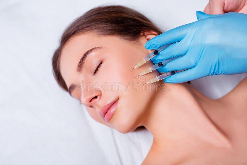 Schönheitseinspritzung Nahaufnahme von Doktor Hands With Syringes nahe weiblichem Gesicht Porträt der Schönheit Gesichtsbehandlun stockbilder