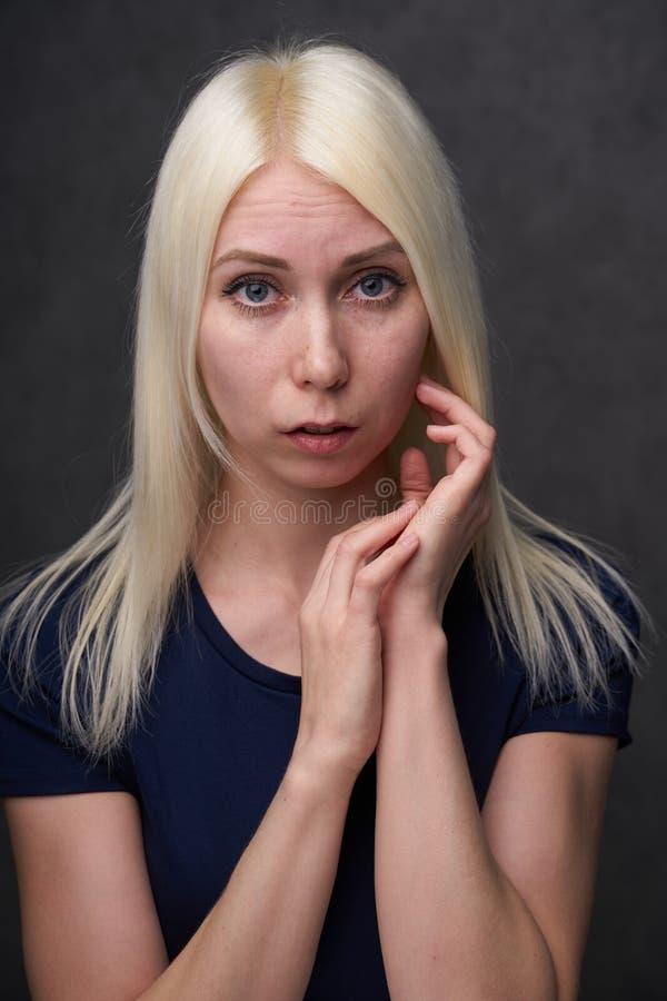 Schönheitsfrau blond in der schwarzen zufälligen Kleidung auf grauem Hintergrund lizenzfreies stockbild