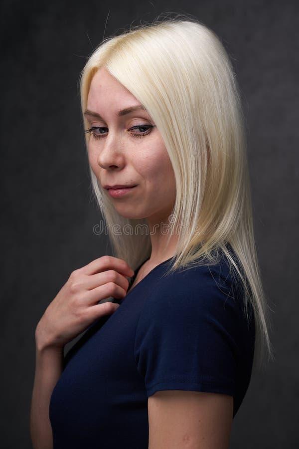 Schönheitsfrau blond in der schwarzen zufälligen Kleidung auf grauem Hintergrund lizenzfreie stockbilder