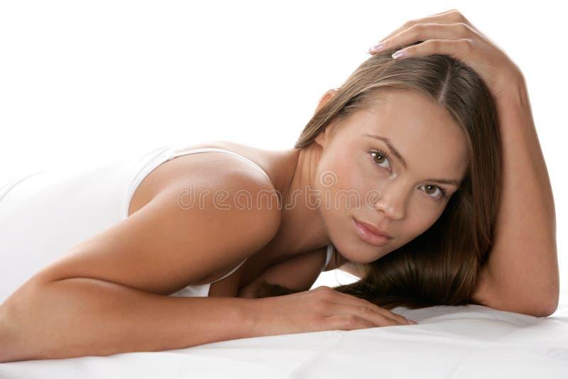 Schönheitsfrau, die auf Magen liegt stockfoto