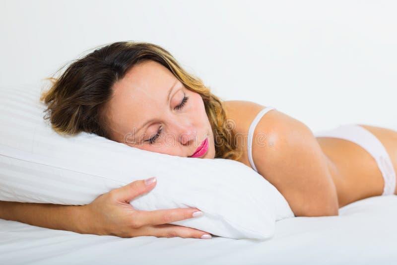 Schönheitsfrau, die auf weißem Kissen schläft lizenzfreies stockbild
