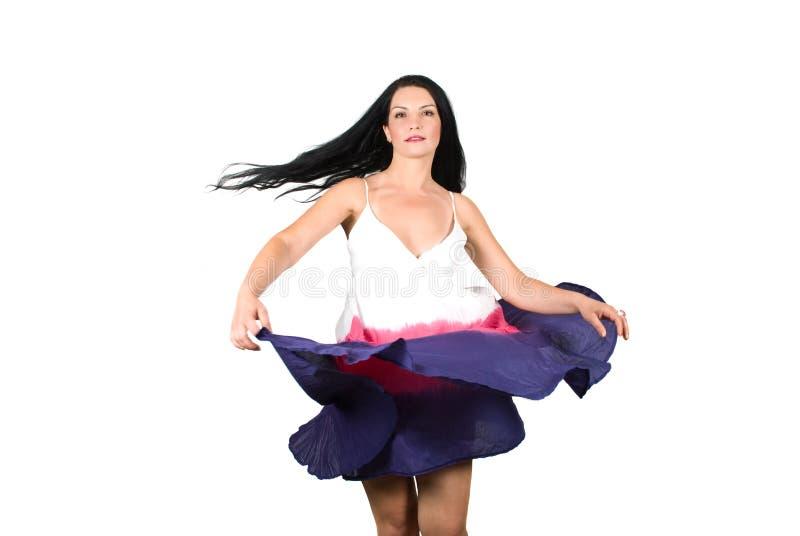 Schönheitsfrau, die ihr Kleid spinnt stockfoto